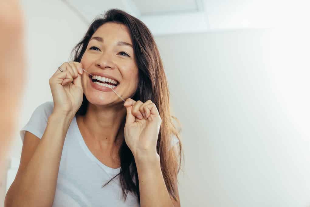 woman flossing for diy teeth whitening